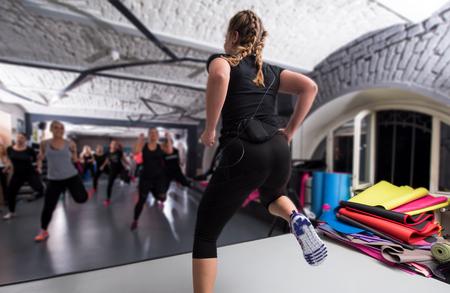 Un groupe de jeunes femmes sportives en bonne santé s'entraînant avec un instructeur faisant des exercices d'aérobic dans un concept de fitness, de sport, d'entraînement, de gym et de style de vie Banque d'images