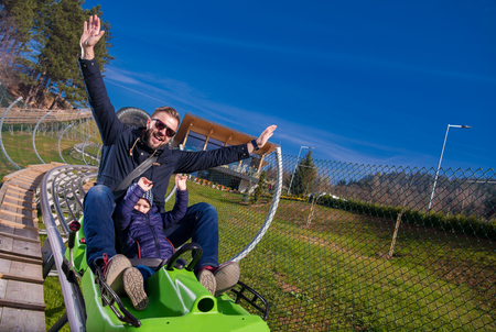 Excited young father and son driving on alpine coaster while enjoying beautiful sunny day in the nature 版權商用圖片 - 122847631