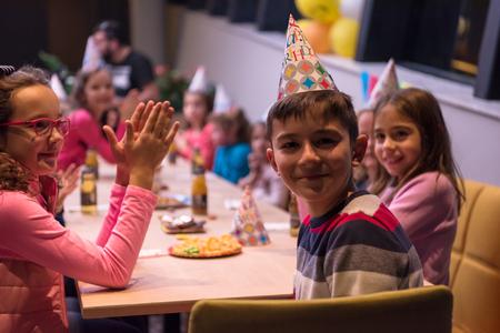De jonge jongen viert vreugdevol zijn verjaardag met een groep van zijn vrienden