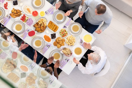 top view of modern multiethnic muslim family praying before having iftar dinner together during a ramadan feast at home 版權商用圖片