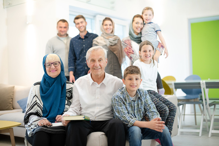 several generations portrait of happy modern muslim family before iftar dinner during ramadan feast at home