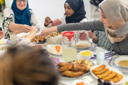 modern multiethnic muslim family enjoying eating iftar dinner together during a ramadan feast at home Imagens