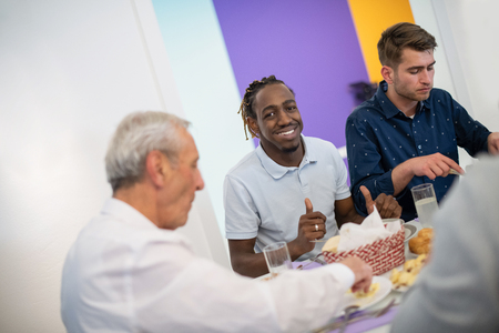 african american man enjoying iftar dinner together with modern multiethnic muslim family during a ramadan feast at home