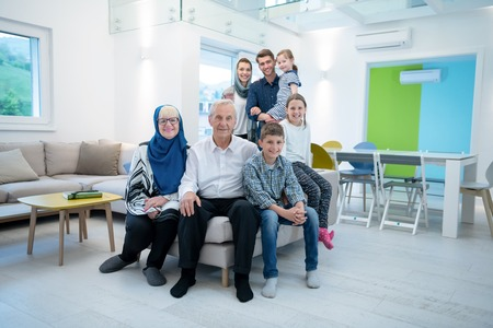 several generations portrait of happy modern muslim family before iftar dinner during ramadan feast at home Foto de archivo - 124546239