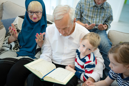 modern muslim family grandparents with grandchildren reading Quran and praying together on the sofa before iftar dinner during a ramadan feast at home 版權商用圖片