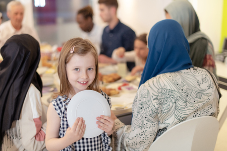 cute little girl enjoying iftar dinner together with modern multiethnic muslim family in the background during a ramadan feast at home