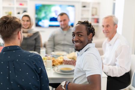 african american man enjoying iftar dinner together with modern multiethnic muslim family during a ramadan feast at home 版權商用圖片