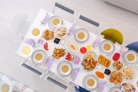 top view of beautiful decorated and served colorful food for iftar dinner on the white table during ramadan feast at home