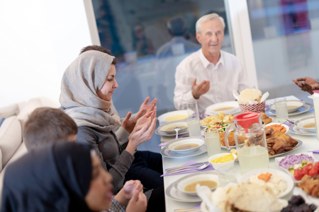 modern multiethnic muslim family praying before having iftar dinner together during a ramadan feast at home Imagens