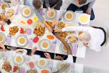 top view of modern multiethnic muslim family enjoying eating iftar dinner together during a ramadan feast at home 版權商用圖片