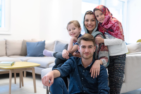 portrait of young happy modern muslim family before iftar dinner during ramadan feast at home