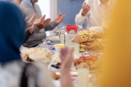 moderne muslimische Familie, die betet, bevor sie während eines Ramadan-Festes zu Hause zusammen ein Iftar-Abendessen isst