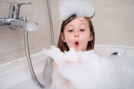 Little girl playing with soap foam in bath