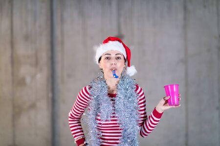 young happy casual business woman wearing a red hat and blowing party whistle while dancing during new years party in front of concrete wall