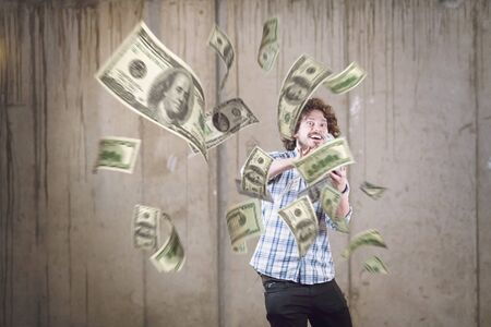 business, people and finances concept  Happy young businessman throwing US dollar banknotes and enjoying while making the rain of money in new startup office Фото со стока