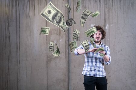 business, people and finances concept  Happy young businessman throwing US dollar banknotes and enjoying while making the rain of money in new startup office Stock Photo