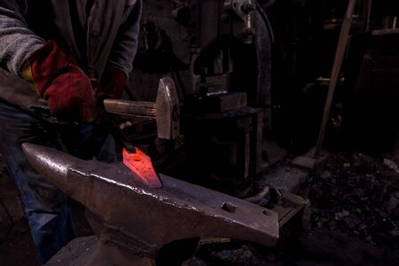 blacksmith manually forging the red hot molten metal on the anvil in traditional smithy workshop. Blacksmith working metal with hammer in the forge