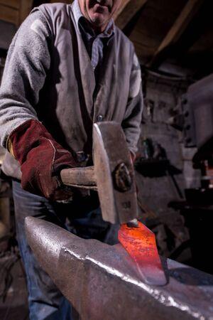 forgeron forgeant manuellement le métal fondu rouge chaud sur l'enclume dans l'atelier de forge traditionnel. Forgeron travaillant le métal avec un marteau dans la forge Banque d'images