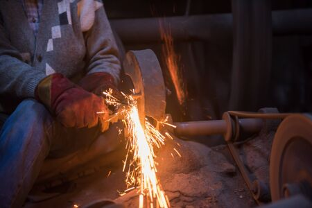 the blacksmith polishing metal products making sparks while using a grinding machine in his traditional workshop