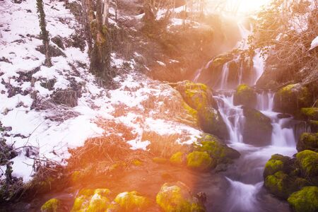Amazing nature landscape, beautiful waterfall with sunlight in deep winter forest
