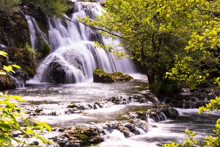 Amazing nature landscape, beautiful waterfall with sunlight in deep summer forest 스톡 콘텐츠 - 127658760