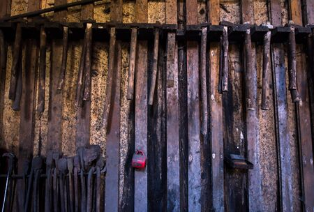 blacksmith tools hanging on a wooden wall
