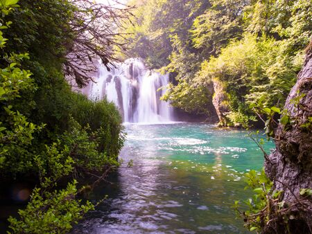 Amazing nature landscape, beautiful waterfall with sunlight in deep summer forest
