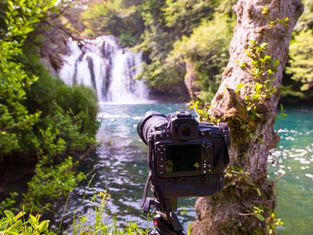 profesional DSLR camera on a tripod at beautiful waterfall with sunlight in deep summer forest