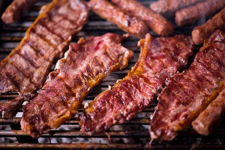 Assorted delicious grilled meat over the coals on barbecue