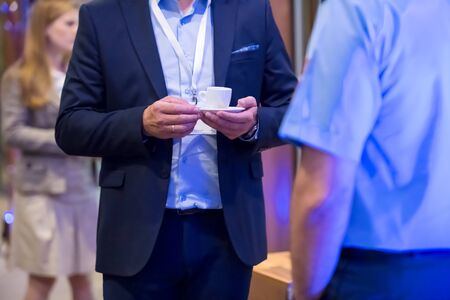 Close up of man hands in a business suit holding a cup of coffee during a business seminar break Stockfoto