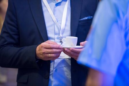 Close up of man hands in a business suit holding a cup of coffee during a business seminar break Фото со стока