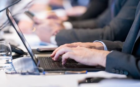 close up shot of business people hands typing on laptop computer keyboard during the business seminar at big modern conference room Banco de Imagens