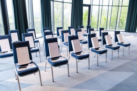 interior of big modern conference room with gifts and headphones on chairs for participants before starting a business seminar Фото со стока
