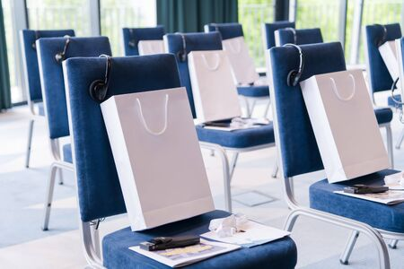 interior of big modern conference room with gifts and headphones on chairs for participants before starting a business seminar Stockfoto