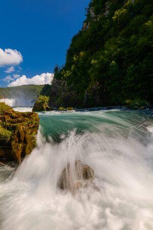 singola pietra nel paesaggio fluviale selvaggio foto a lunga esposizione che rappresenta il concetto di flusso di liquido