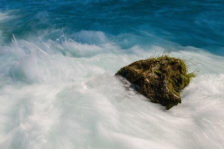 single stone in wild river landscape  long exposure photo representing liquid flow concept 写真素材