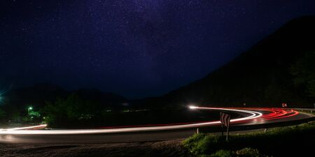 vegicle light trails in night on busy countryroad curve  long exposure