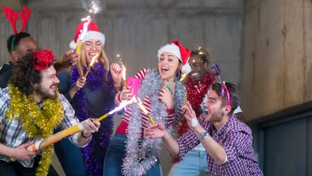 multiethnic group of young happy casual business people dancing with sparklers and having fun while celebrating new year eve in front of concrete wall at new startup office