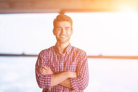 portrait of young casual businessman standing with crossed arms on construction site and sunlight through the windows during moving in at new startup office