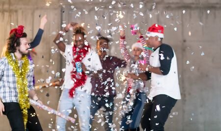 multiethnic group of young happy casual business people dancing and having confetti party while celebrating new year eve in front of concrete wall at new startup office