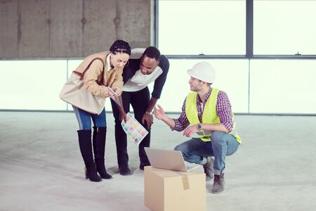 architect engineer using laptop computer while showing house design plans to a young multiethnic couple at construction site