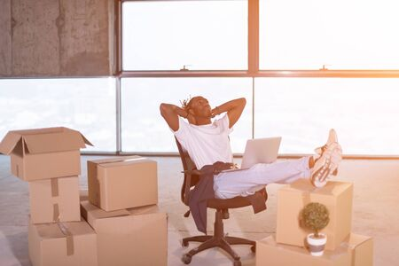 young african american casual businessman taking a break on construction site while checking business workflow using laptop computer with sunlight through the windows and cardboard boxes around him in