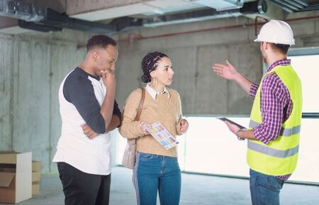 architect engineer using tablet computer while showing house design plans to a young multiethnic couple at construction site