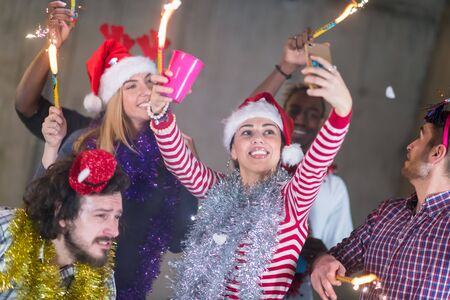 multiethnic group of young happy casual business people taking selfie picture while dancing with sparklers and having fun during new year party in front of concrete wall at new startup office Stock Photo