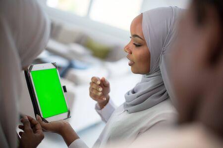 Grupo de estudiantes africanos felices conversando y reuniéndose en equipo trabajando juntos en la tarea niñas vistiendo la moda tradicional hijab musulmán de Sudán
