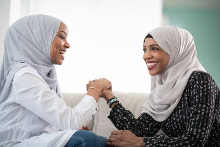 African woman  arm wrestling conflict concept, disagreement and confrontation wearing traditional islamic hijab clothes