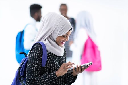 african female student with group of friends in background  wearing traditional Islamic hijab clothes