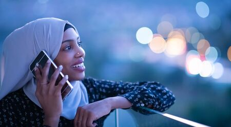 Young Muslim woman wearing scarf veil on urban city  street at night texting on smartphone with bokeh city light in background Standard-Bild