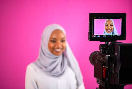 male videographer in digital studio recording video on professional camera by shooting female muslim woman wearing hijab scarf plastic pink background
