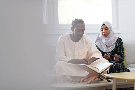 african muslim couple at home in ramadan reading quran holly islam book